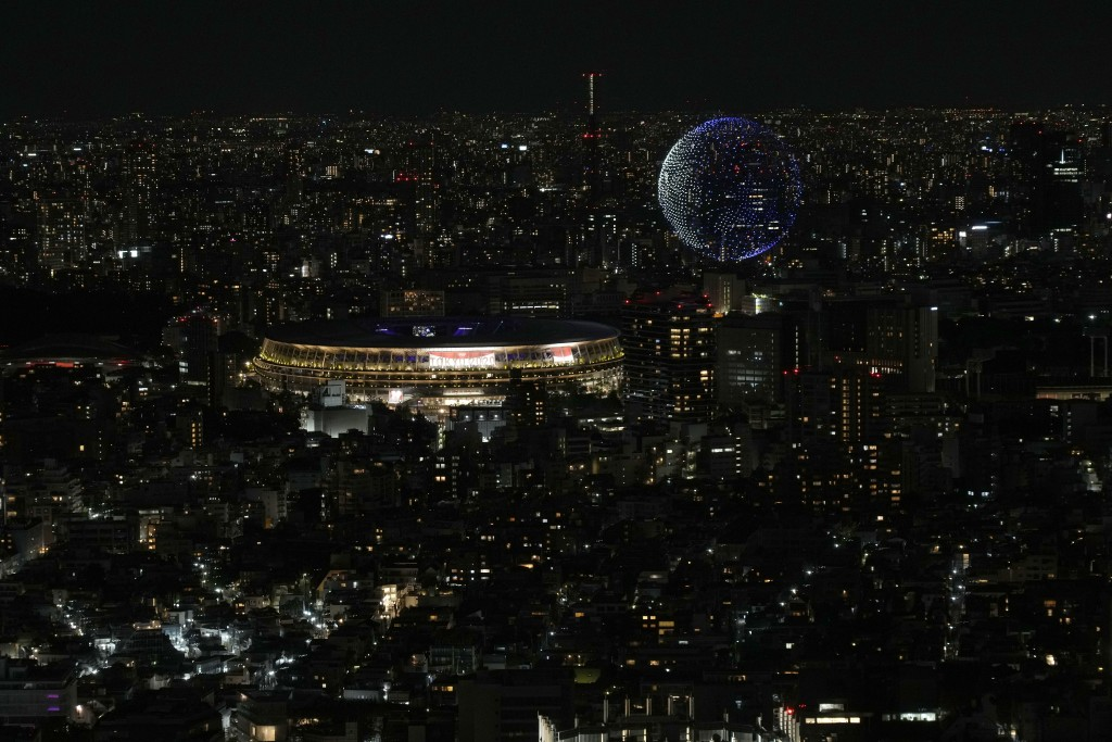 FILE - In this July 23, 2021, file photo, drones fly over the National Stadium during the opening ceremony of 2020 Tokyo Olympics is seen from Shibuya...