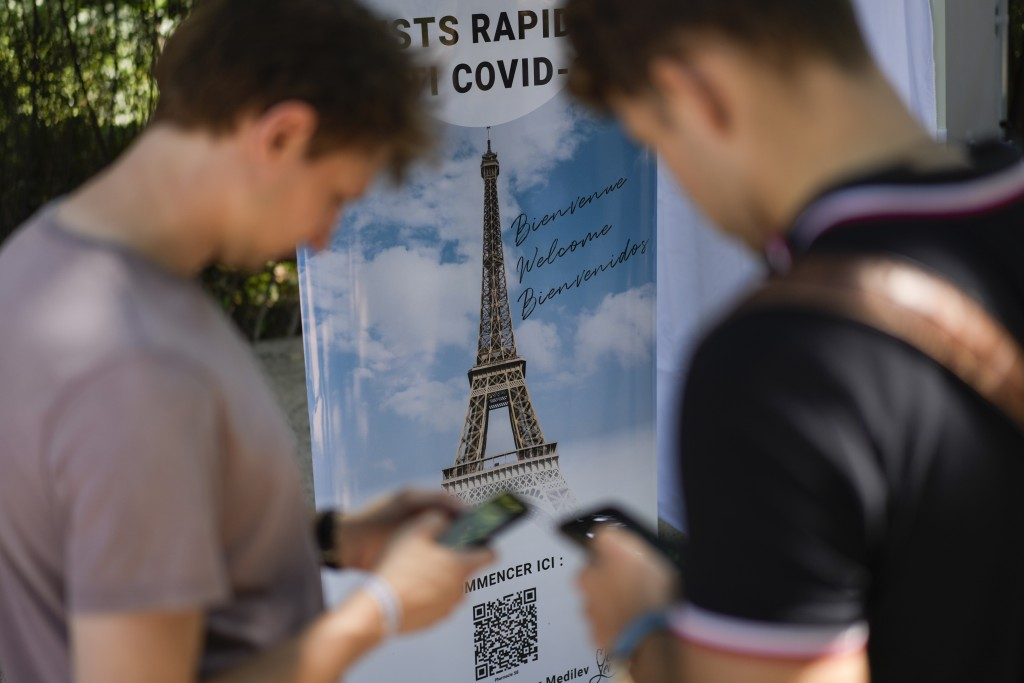FILE  - In this Wednesday, July 21, 2021 file photo, visitors register for COVID-19 tests at the Eiffel Tower in Paris. For Europe's battered tourism ...