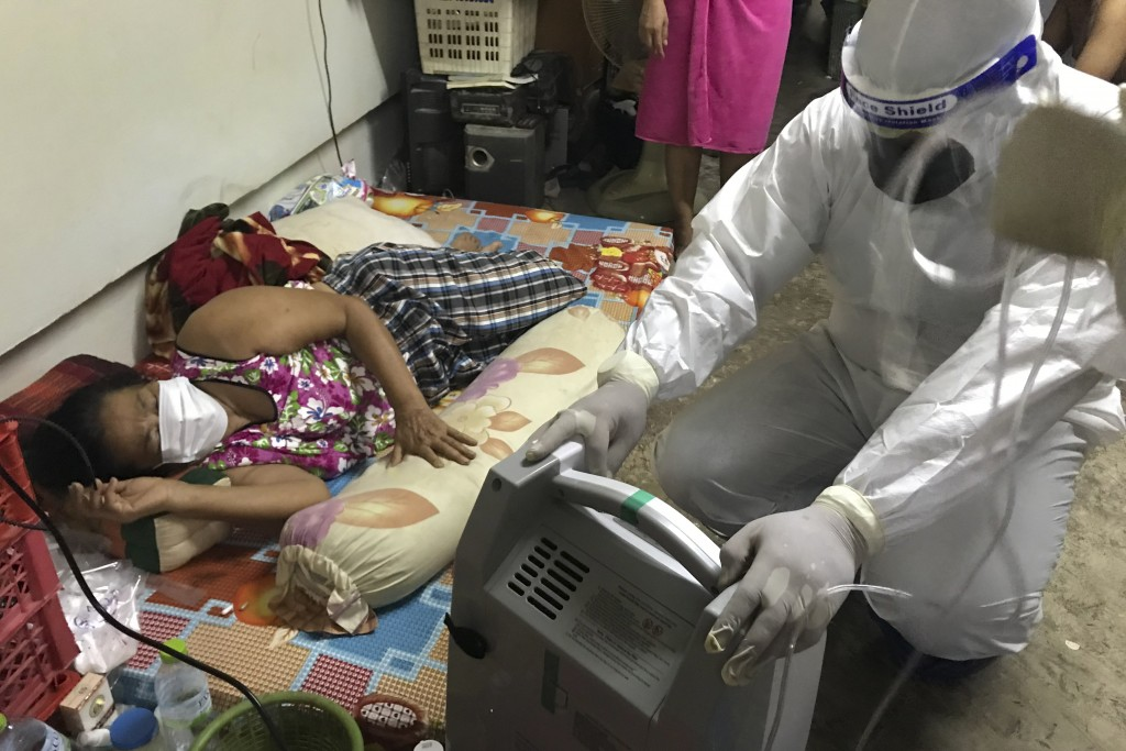 A member of the volunteer Saimai Must Survive Group prepares a home oxygen concentrator to help a woman infected with the COVID-19 with difficulty bre...