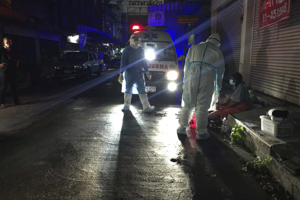 Volunteers from the 'Saimai Will Survive' group arrive with an ambulance in protective gear to help a homeless woman infected with COVID-19 on a sidew...