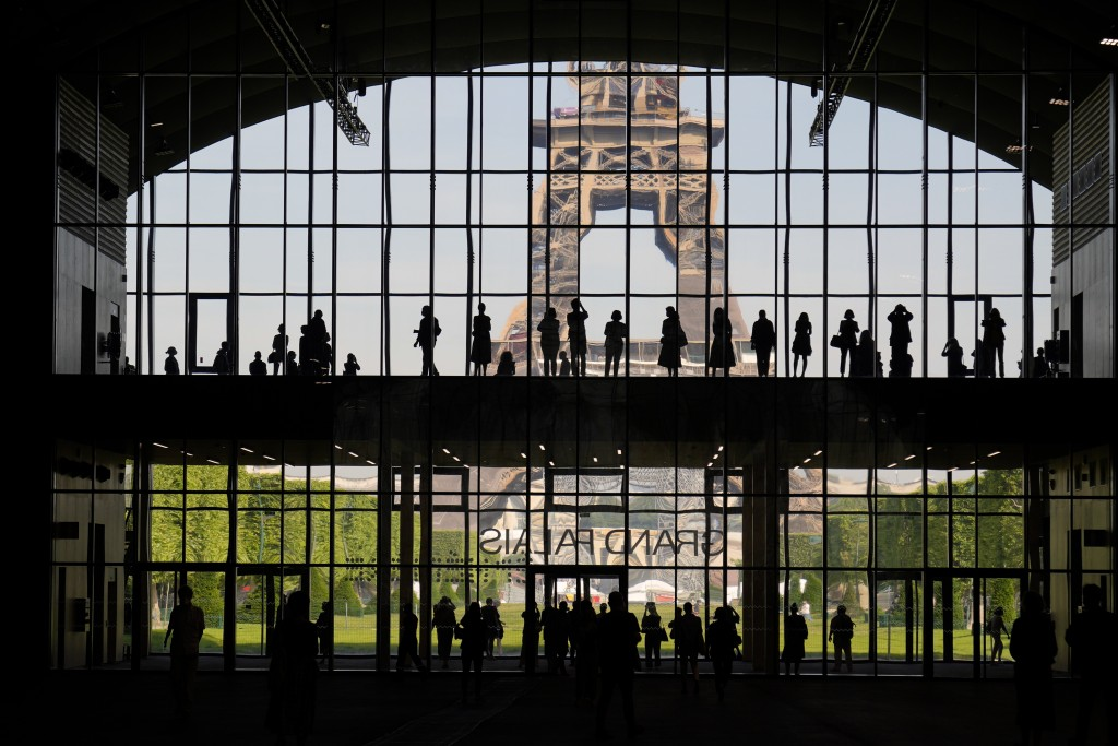 """FILE - In this Wednesday, June 9, 2021 file photo, visitors gather during a presentation visit of the """"Grand Palais Ephemere"""", with the Eiffel Tower i..."""