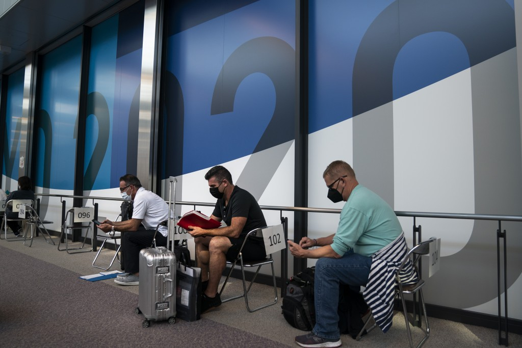 FILE - In this July 10, 2021, file photo, visitors wait in the holding area to take a COVID-19 test at the Narita International Airport in Narita, nea...