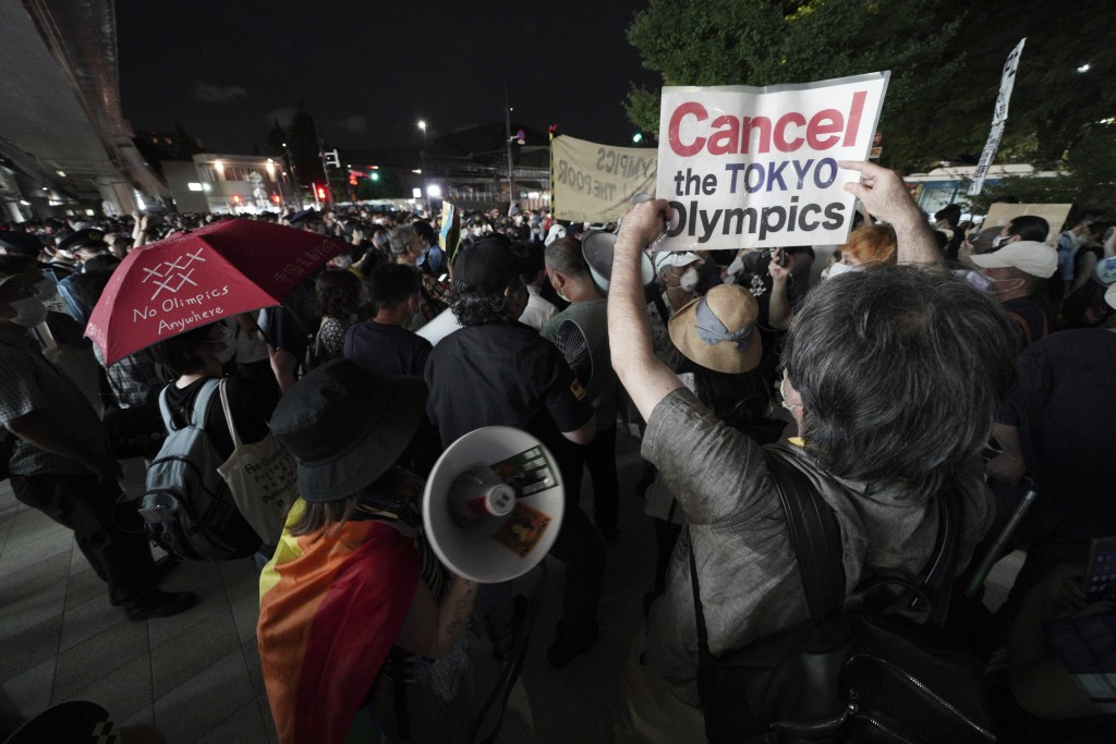 FILE - In this July 23, 2021, file photo, people protest against the Olympics near the National Stadium in Tokyo, Japan where the opening ceremony of ...