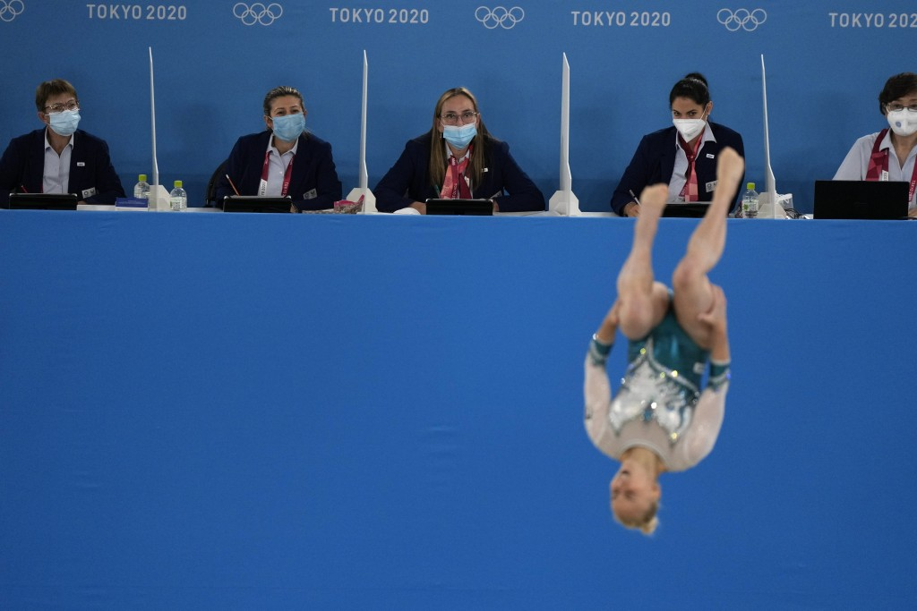 FILE - In this July 25, 2021, file photo, judges evaluate Asia D'Amato, of Italy, performing her floor exercise during the women's artistic gymnastic ...