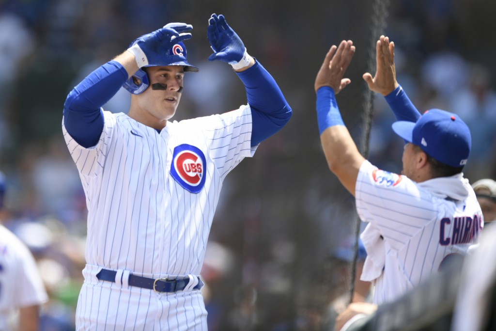 Chicago Cubs' Anthony Rizzo left, celebrates at the dugout with teammate Robinson Chirinos right, after hitting a solo home run during the first innin...