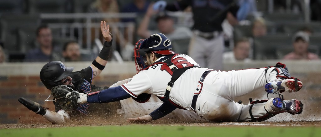Miami Marlins' Eddy Alvarez, left, slides safe to score past the tag of Atlanta Braves catcher Travis d'Arnaud in the ninth inning of a baseball game ...