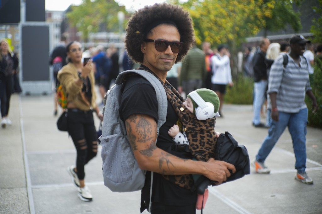 A father carrying his baby with ear protection keeps a safe distance as he joins a protest of organizers and fans of music festivals stage against the...