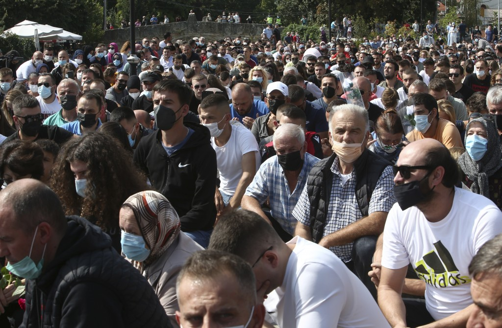 People kneel to honor the victims of the fire, near the burned out makeshift hospital, in North Macedonia's northwestern town of Tetovo, Saturday, Sep...