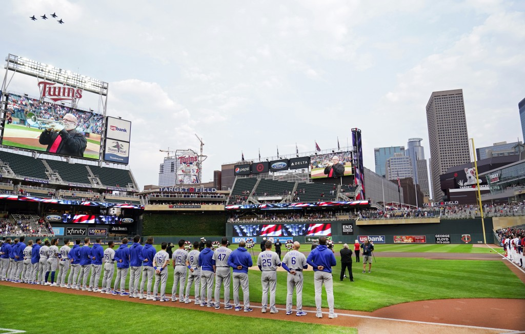 Four fighter jets, upper left, fly over Target Field where players from the Minnesota Twins and the Kansas City Royals observed a moment of silence to...