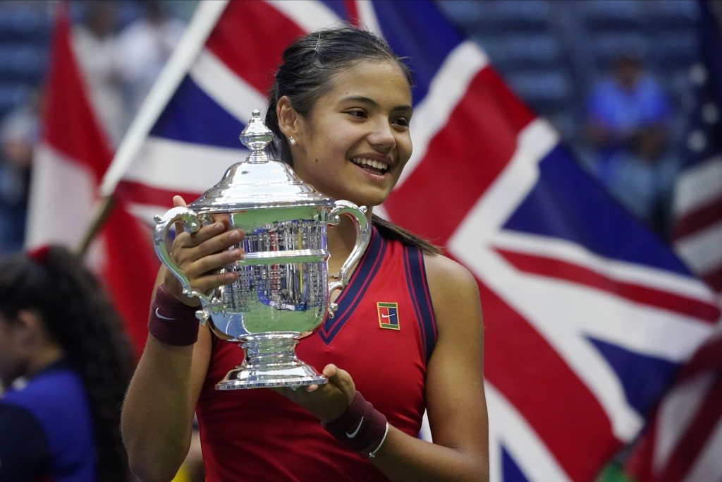 Emma Raducanu, of Britain, holds up the US Open championship trophy after defeating Leylah Fernandez, of Canada, during the women's singles final of t...