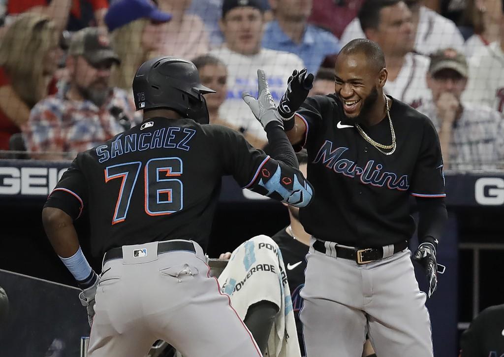 Miami Marlins' Jesus Sanchez (76) and Bryan De La Cruz celebrate their back to back home runs off Atlanta Braves' Richard Rodriguez in the eighth inni...