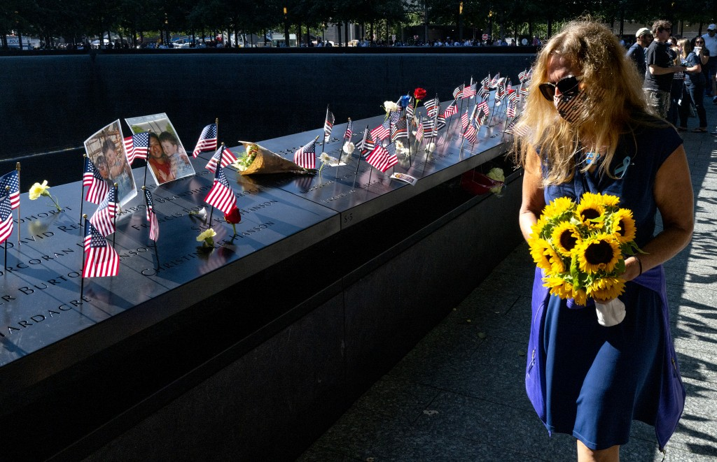 Flags adorn the inscribed names of the victims of Sept. 11, 2001, at the National September 11 Memorial in New York on the 20th anniversary of the att...