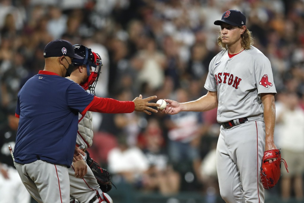 Boston Red Sox manager Alex Cora, left, takes the ball from relief pitcher Garrett Richards, right, during the fourth inning of a baseball game agains...