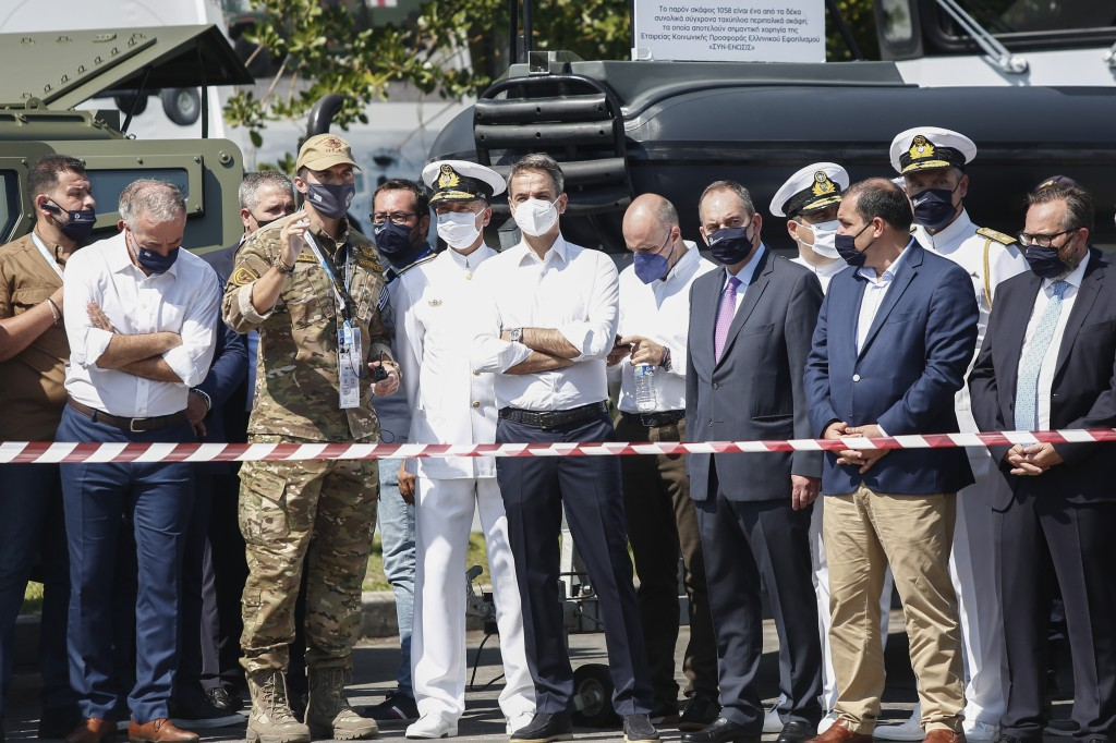 Greece's Prime Minister Kyriakos Mitsotakis, center, stands next to a Hellenic Coast Guard's Special Forces member, during a visit to Thessaloniki Int...