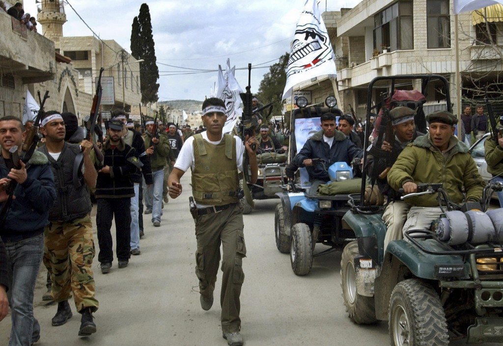 FILE - In this April 2, 2005 file photo, Zakaria Zubeidi, center, then local leader of the Al Aqsa Martyrs Brigades and other militants march in the W...