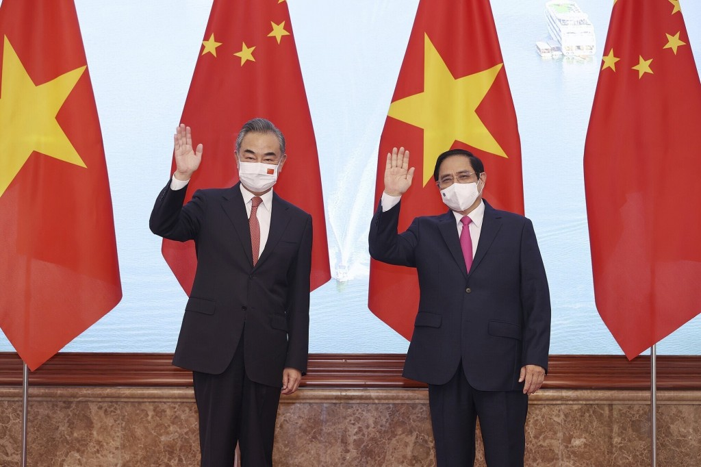 Vietnamese Prime Minister Pham Minh Chinh and Chinese Foreign Minister Wang Yi wave as they stand for photos in Hanoi, Vietnam on Saturday, Sep.11, 20...
