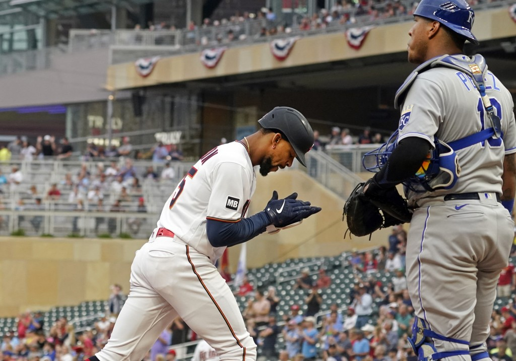 Minnesota Twins' Byron Buxton, left, applauds in front of Kansas City Royals catcher Salvador Perez, right, as he scores on his solo home run off Roya...