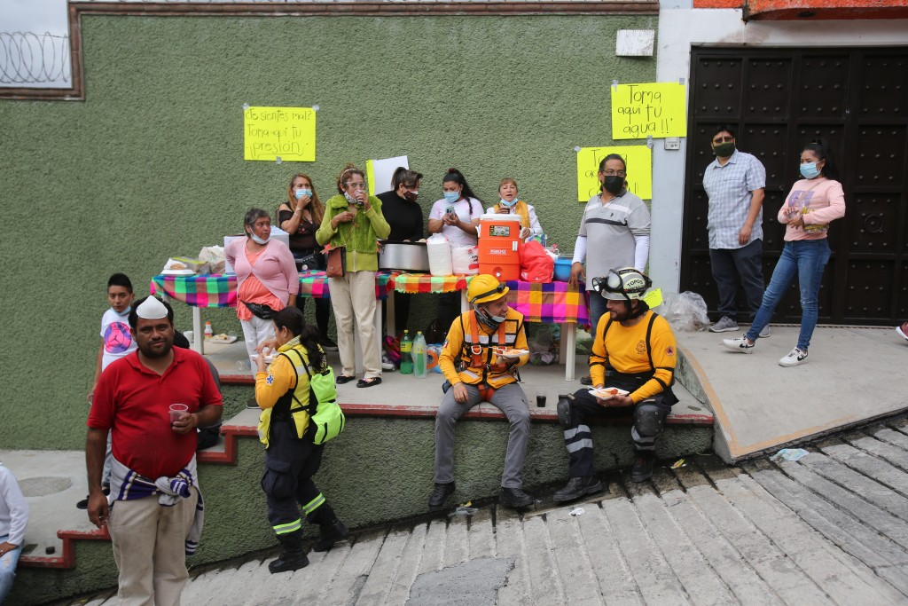 Volunteers offer free food and drink for search and rescue team members at the site of a landslide that brought tons of massive boulders down on a ste...