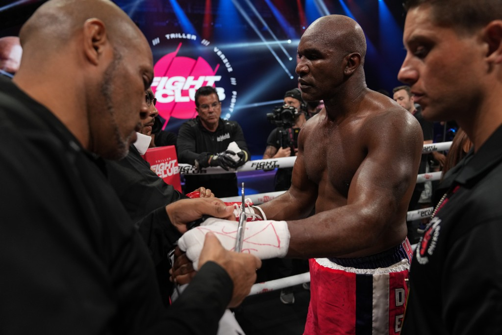 Former heavyweight champion Evander Holyfield, center, has his gloves and hand wraps removed after losing in the first round of a boxing match against...