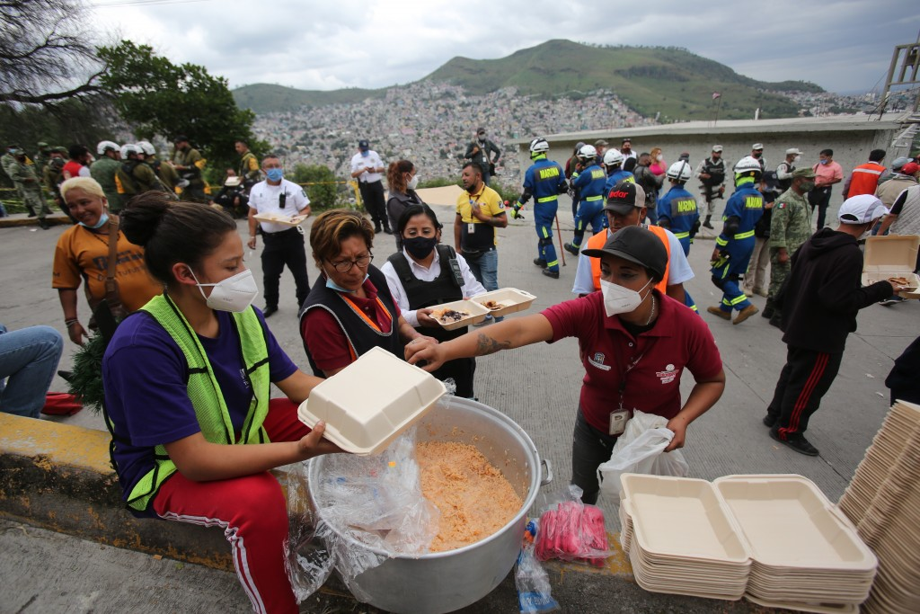 Volunteers prepare plates of food for people working in the search and rescue efforts at the site of a landslide that brought tons of massive boulders...
