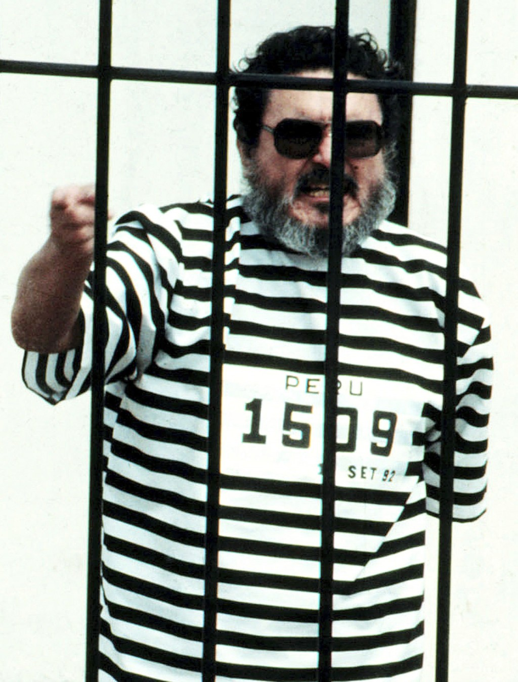FILE - In this Sept. 1992 file photo, Abimael Guzman, the founder and leader of the Shining Path guerrilla movement, shouts inside of a jail cell afte...
