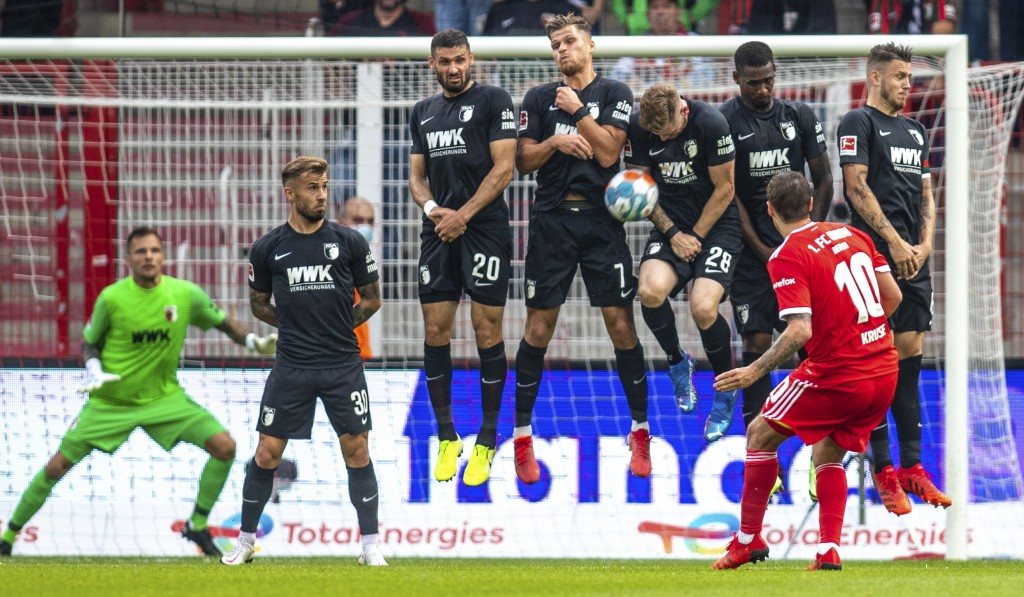 Berlin's Max Kruse shoots a free kick against FC Augsburg's defense during a German Bundesliga soccer match between Union Berlin and FC Augsburg in Be...