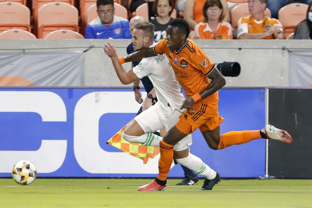Austin FC midfielder Tomas Pochettino, left, is pushed by Houston Dynamo defender Teenage Hadebe (18) as they chase the ball during the first half of ...