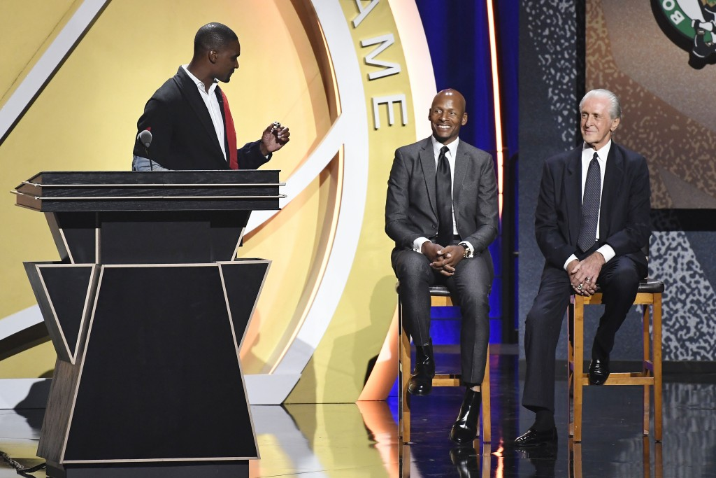Inductee Chris Bosh holds up a ring to give to Pat Riley, right, as Ray Allen looks on during the 2021 Basketball Hall of Fame Enshrinement ceremony, ...