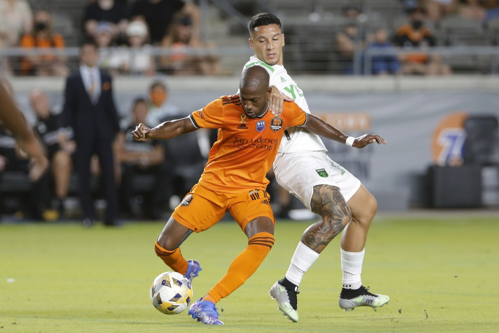 Houston Dynamo midfielder Fafa Picault (10) is pulled back as he moves the ball by Austin FC midfielder Sebastian Driussi (25) during the first half o...