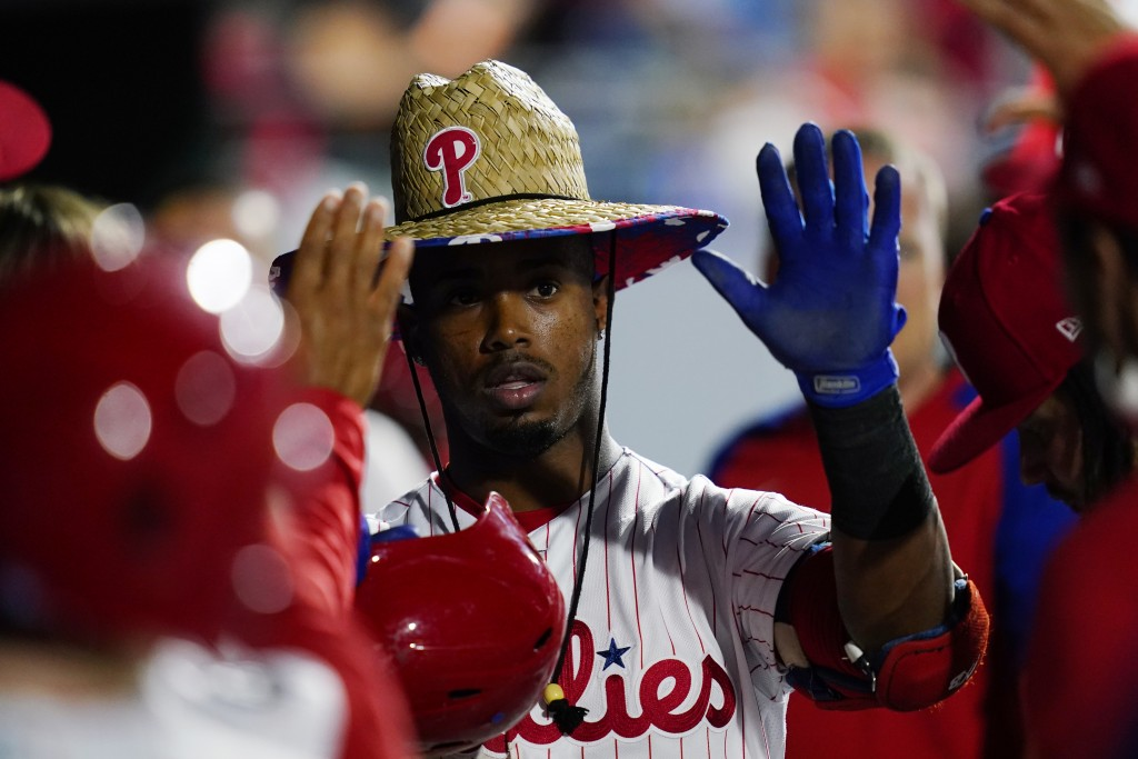 Philadelphia Phillies' Jean Segura celebrates in the dugout after hitting a home run off Colorado Rockies pitcher Kyle Freeland during the fifth innin...