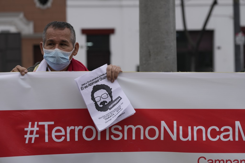"""A man helps hold up a banner with a hashtag that reads in Spanish; """"Terrorism never again"""" as he joins others outside the anti-terrorism directorate t..."""