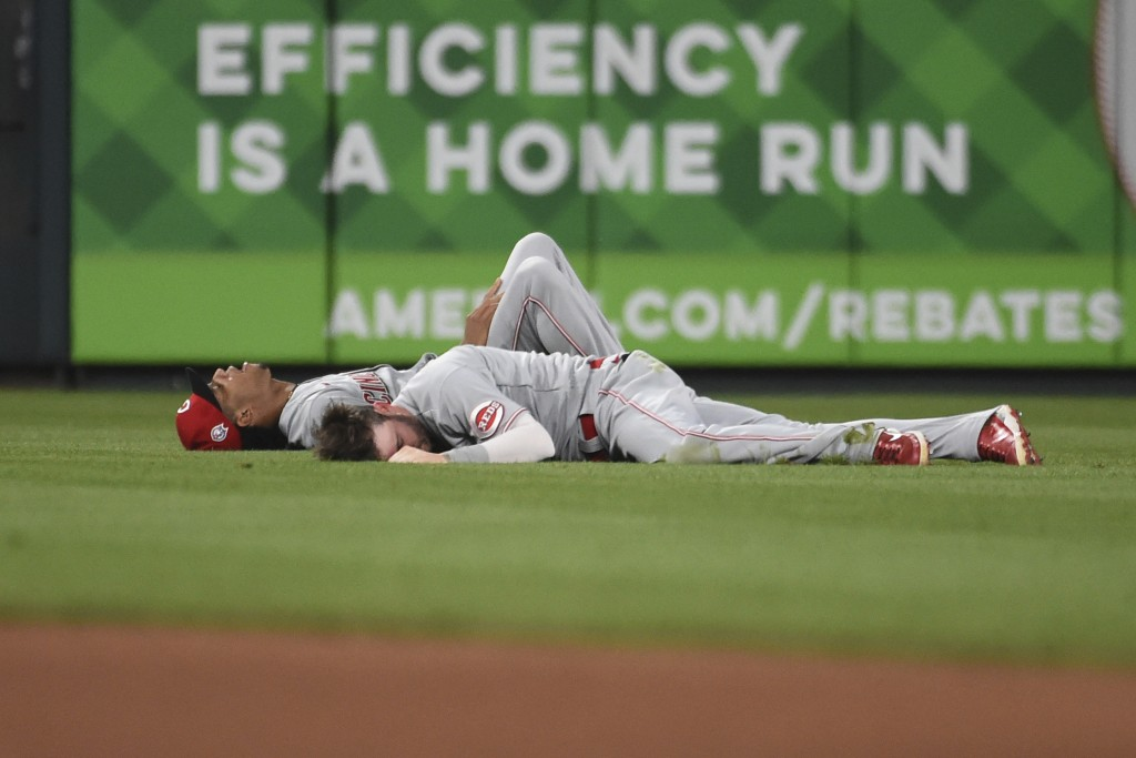 Cincinnati Reds center fielder Tyler Naquin and shortstop Jose Barrero lie on the grass after colliding during the sixth inning of a baseball game aga...