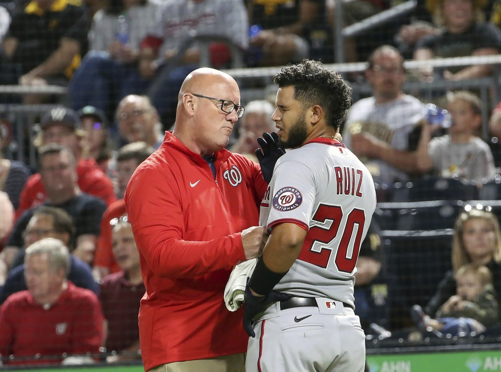 Washington Nationals' Keibert Ruiz (20) is checked out by athletic trainer Paul Lessard after being hit by a pitch in the sixth inning of a baseball g...