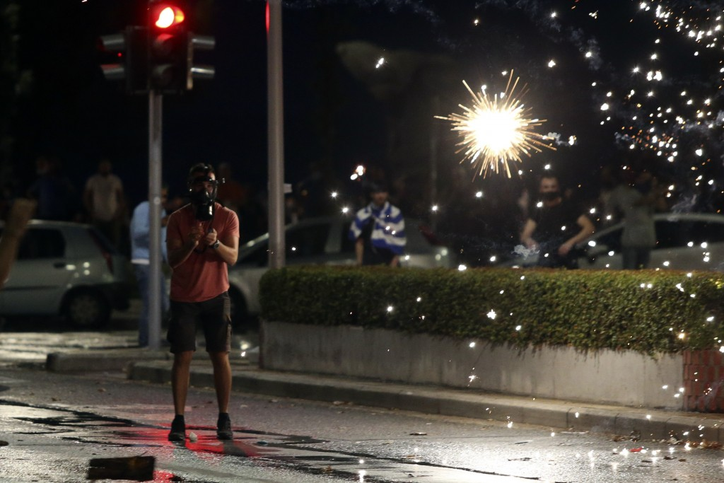 A fire cracker explodes in front of an anti-vaccine protester during a rally, at the northern city of Thessaloniki, Greece, Saturday, Sept. 11, 2021. ...