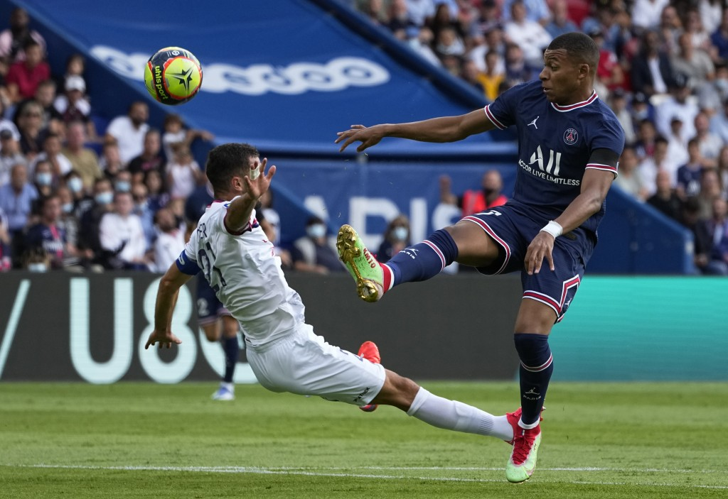 PSG's Kylian Mbappe, right, kicks the ball ahead of Clermont's Florent Ogier during the French League One soccer match between Paris Saint-Germain and...