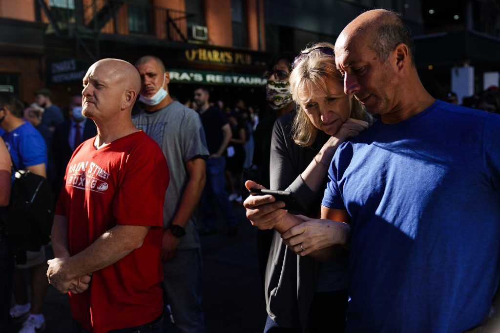 A couple gathers with others outside the National September 11 Memorial and Museum as they view on their smartphone a ceremony marking the 20th annive...