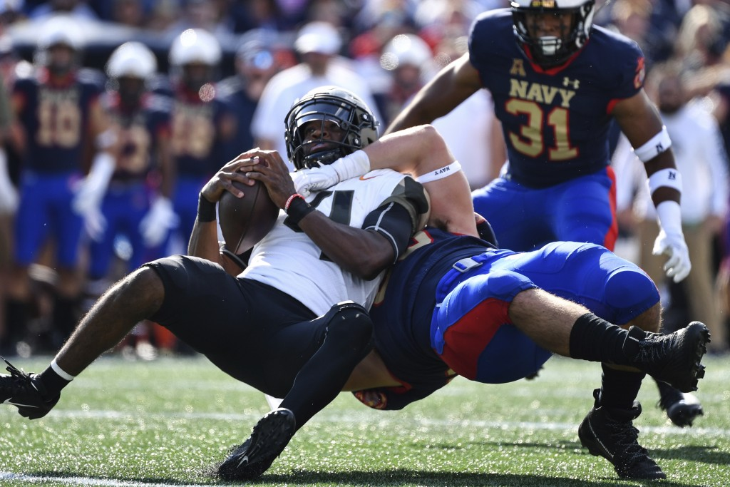 Air Force quarterback Haaziq Daniels left, is tackled by Navy defensive end Jacob Busic (95) during the first half of an NCAA college football game, S...
