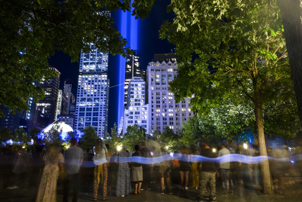 """A crowds looks at the annual """"Tribute in Light"""" illuminated on the 20th anniversary of the Sept. 11 attacks on Saturday, Sept. 11, 2021, in New York. ..."""