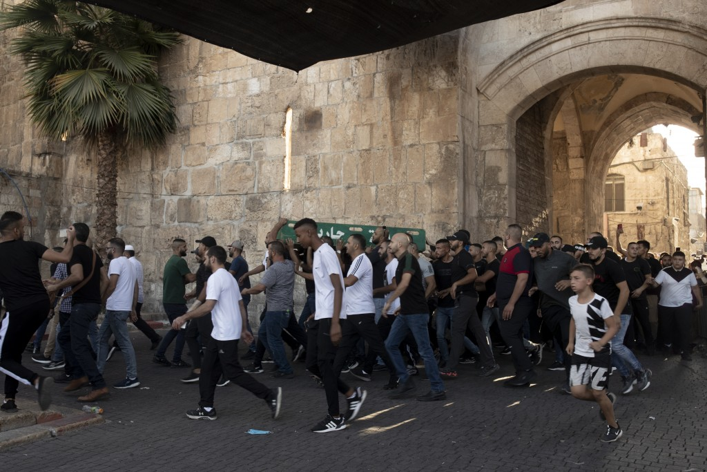 Palestinian protesters march into the Al Aqsa Mosque compound in the Old City of Jerusalem, Friday, Sept. 10, 2021. Amid increased Israeli-Palestinian...