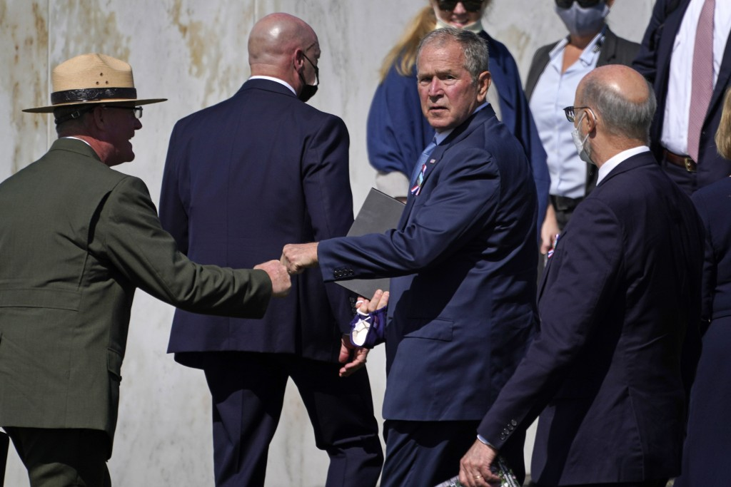 Former President George W. Bush, right center, bumps fists with Flight 93 National Memorial superintendent Stephen M. Clark, left, after participating...