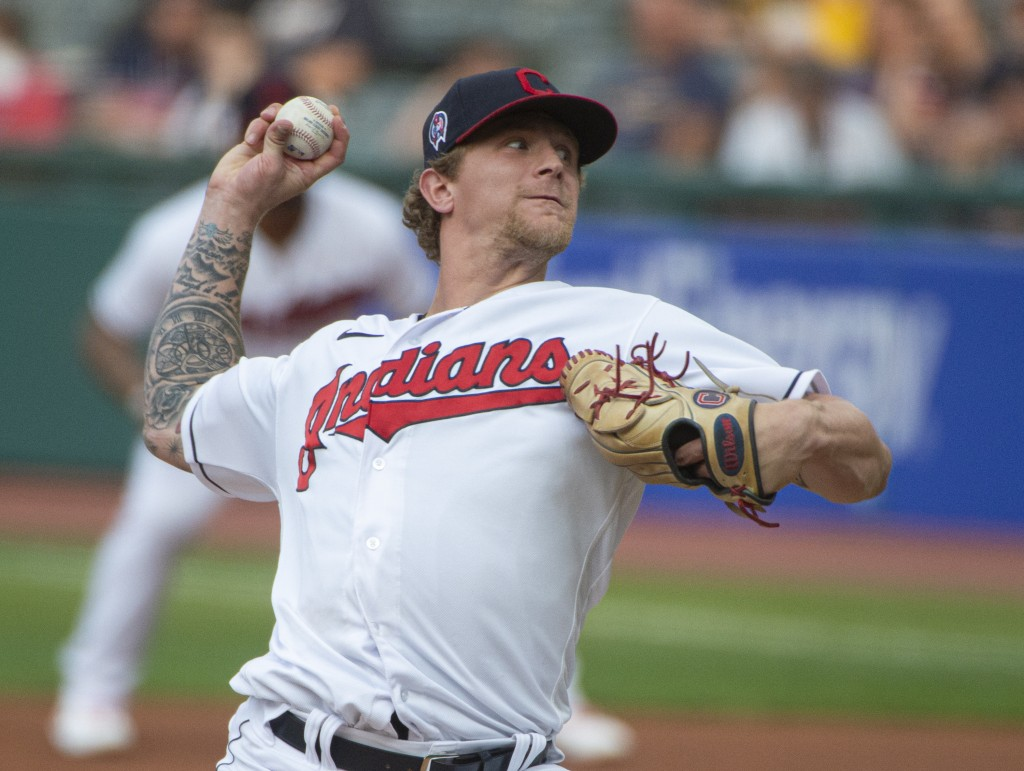 Cleveland Indians starting pitcher Zach Plesac delivers against the Milwaukee Brewers during the first inning of a baseball game in Cleveland, Saturda...