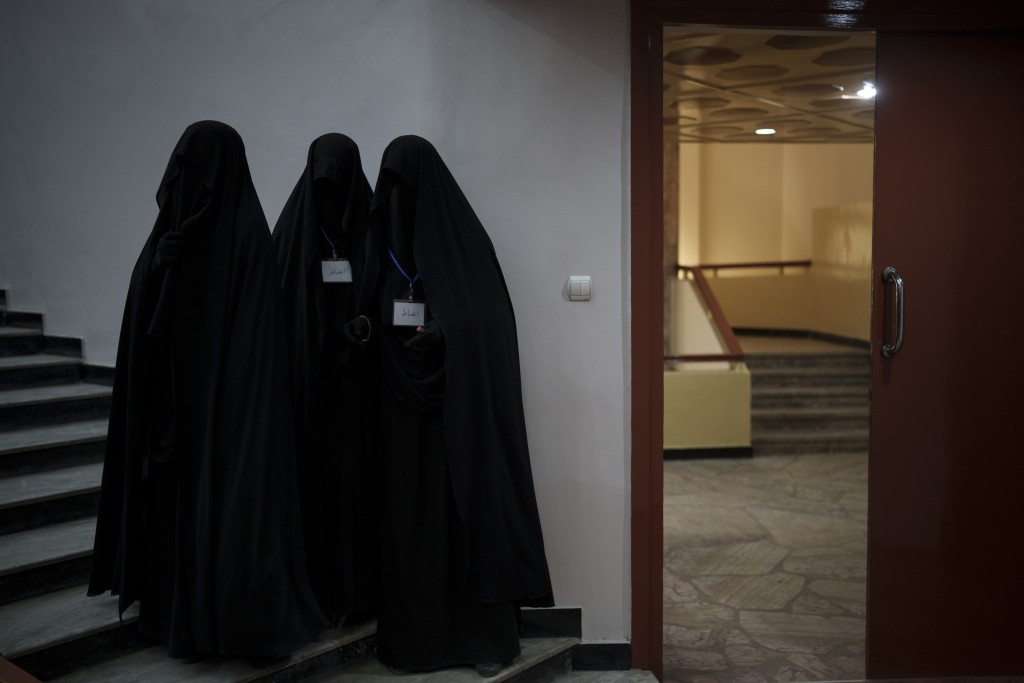 Women stand inside an auditorium at Kabul University's education center during a demonstration in support of the Taliban government in Kabul, Afghanis...