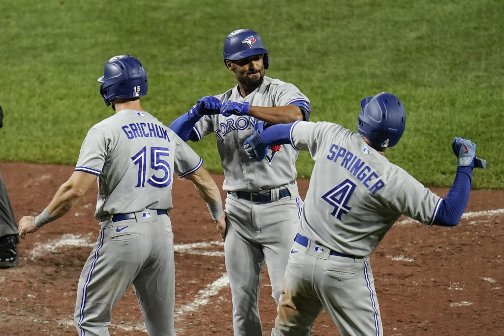 Toronto Blue Jays' Marcus Semien, center, celebrates with Randal Grichuk (15) and George Springer (4) after Semien scored all three of them on a three...