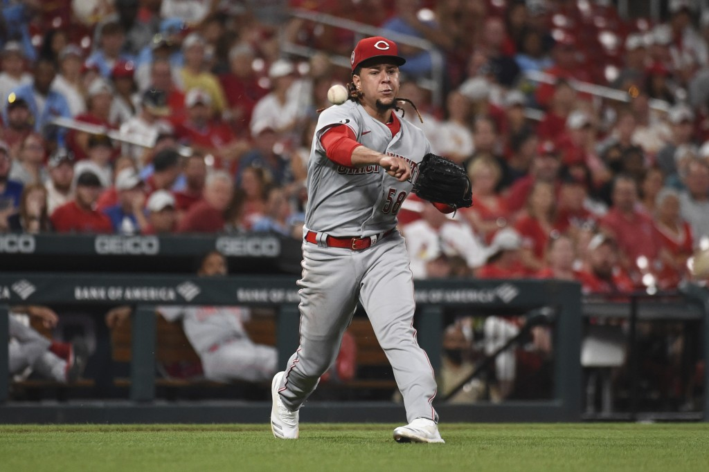 Cincinnati Reds starting pitcher Luis Castillo attempts to throw out St. Louis Cardinals' Tyler O'Neill at first base during the sixth inning of a bas...