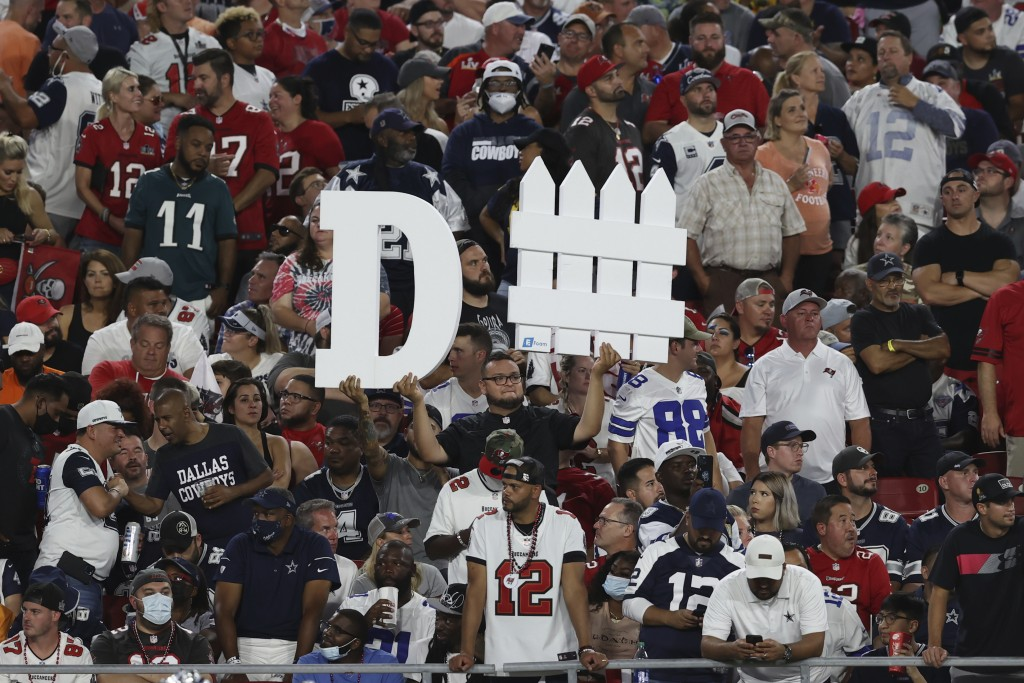 A Tampa Bay Buccaneers fan holds a sign during the first half of an NFL football game against the Dallas Cowboys Thursday, Sept. 9, 2021, in Tampa, Fl...