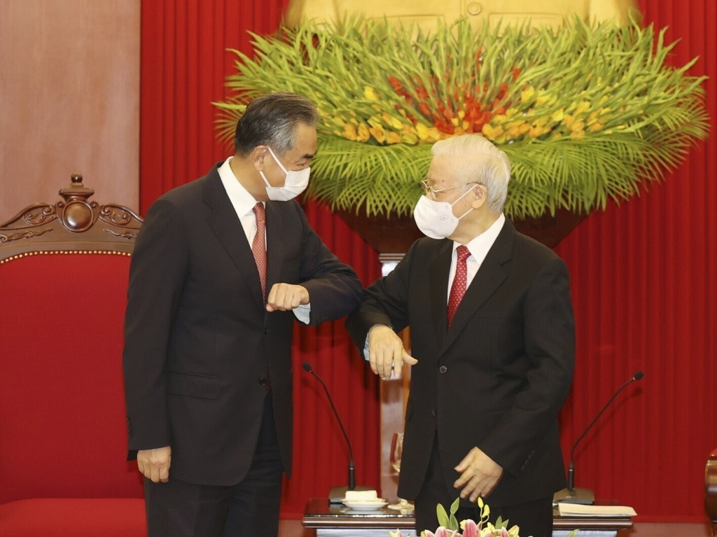 Vietnamese Communist Party General Secretary Nguyen Phu Trong and Chinese Foreign Minister Wang Yi elbow as they meet in Hanoi, Vietnam on Saturday, S...