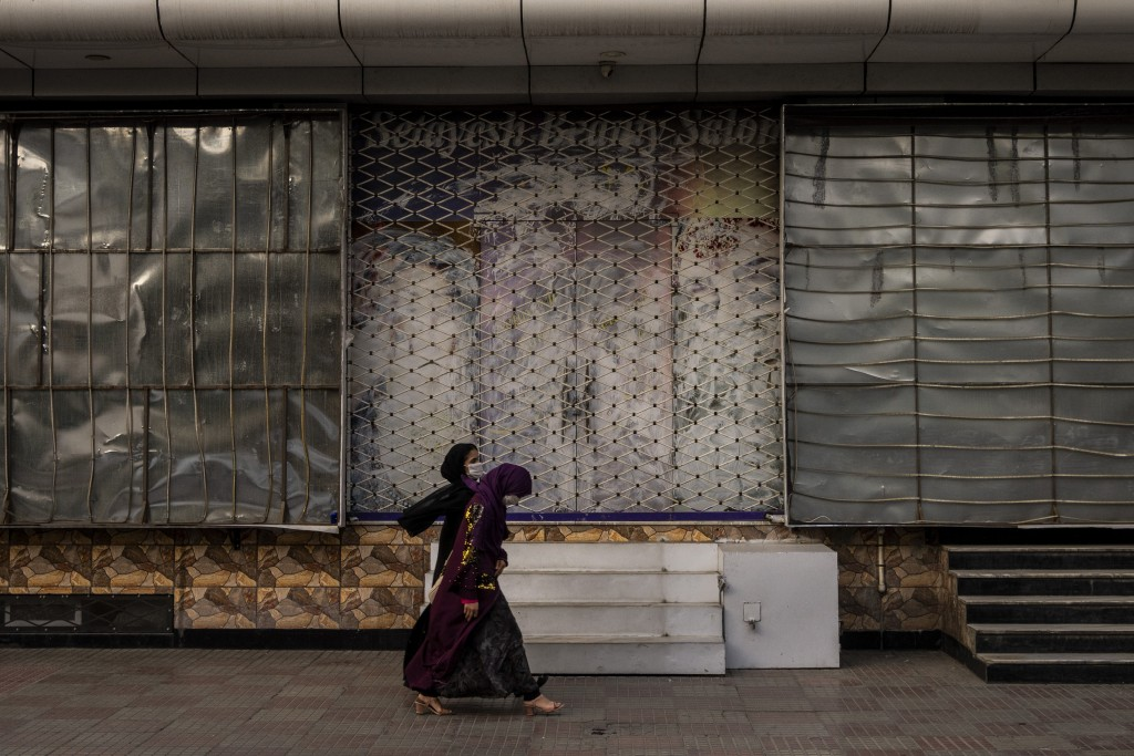 Afghan women walk past a closed beauty salon in Kabul, Afghanistan, Saturday, Sept. 11, 2021. Since the Taliban gained control of Kabul, several image...