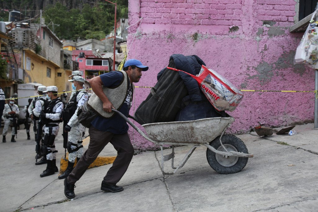 An evacuee uses a wheelbarrow to transport his belongings away from the site of a landslide that brought tons of massive boulders down on a steep hill...