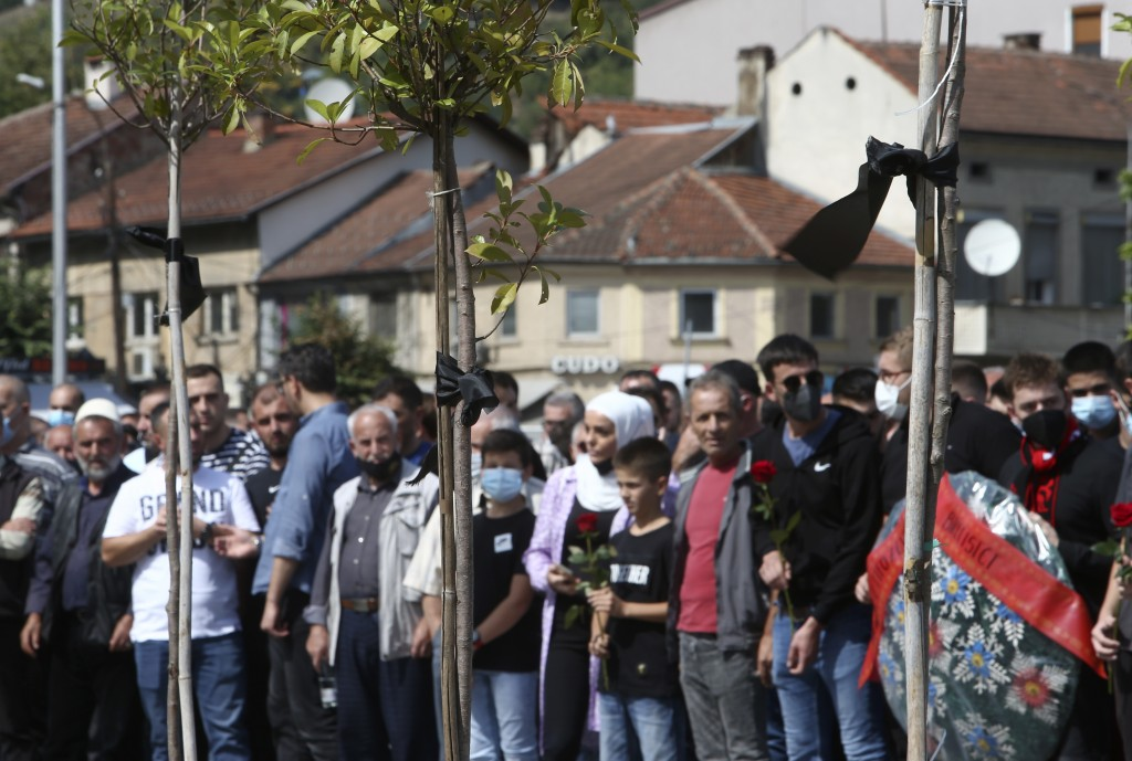 Black ribbons are tied to the trees as people are gathering to honor the victims of the fire in a hospital, in North Macedonia's northwestern town of ...