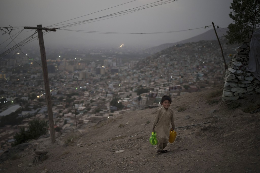 A boy carries water to his home atop a hill in Kabul, Afghanistan, Saturday, Sept. 11, 2021. (AP Photo/Felipe Dana)